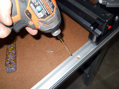 Move the plotter/cutter down the track, drilling and securing each track hole as you go.