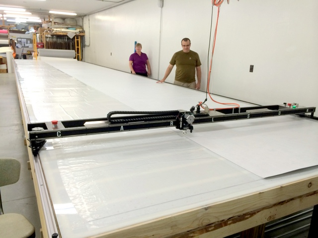 This project is cut in Tyvek.  To begin, pull the roll the length of the table and align it with the plotted alignment mark.  They are building a new roll holder to make spreading even easier.