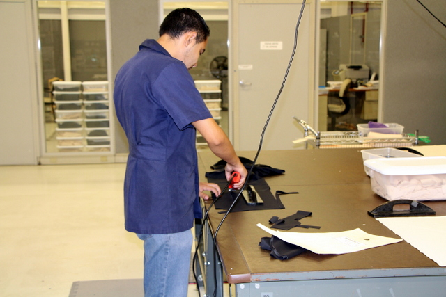An electric rotary cutter is guided by hand around the pattern by a skilled operator.