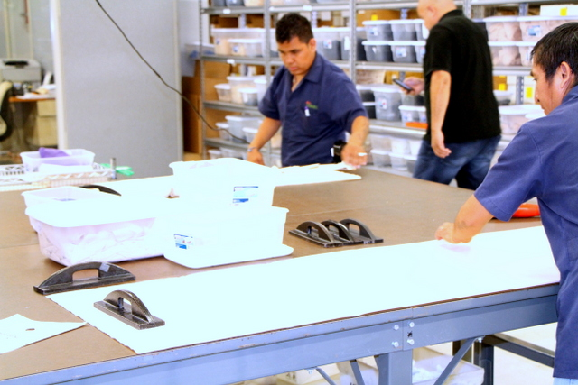 Material, templates, and weights are stacked for hand cutting.