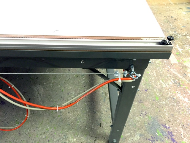 Secure the cables at the end of the table and then run them toward the operator's workstation.
