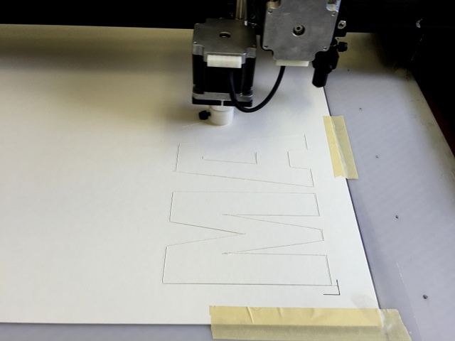 Cutting a stencil out of Chipboard.