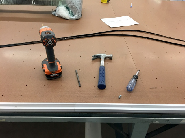Punch, drill a pilot hole, and then hand screw the track to the table.