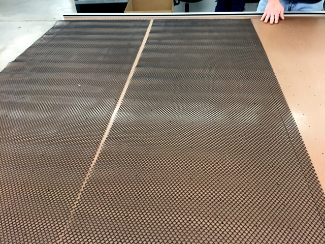 """Spread """"breather"""" mesh across the width of the table.  This creates an air channel between the cutting surface and the vacuum top."""